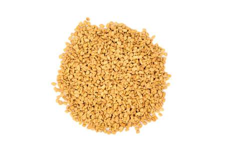 Pile of dry grains of fenugreek on a white background top view Zdjęcie Seryjne