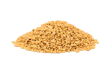 Pile of dry grains of fenugreek on a white background