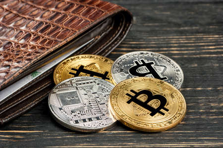 Female hand putting a gold coin in the bitcoin wallet on white scattered gold and silver coins with the bitcoin wallet closeup photo ccuart Choice Image