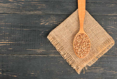 Spoonful of raw buckwheat on sackcloth and empty wooden background