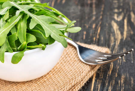 Fresh leaves of arugula in a bowl with a fork on the table Stock Photo
