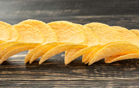 Scattered potato chips on a dark table closeup Stock Photo