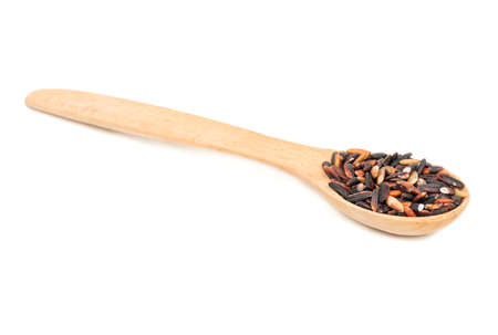 Small wooden spoon with raw black rice isolated on white background Stock Photo
