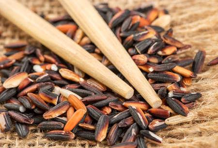 Raw black wild rice with chopsticks on burlap close-up