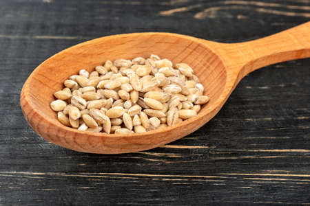 Pearl barley in spoon on wooden background closeup 스톡 콘텐츠