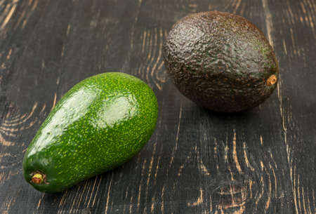 Black and green avocado on a dark table closeup