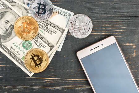 Gold and silver bitcoin coins with dollars and smartphone on wooden background