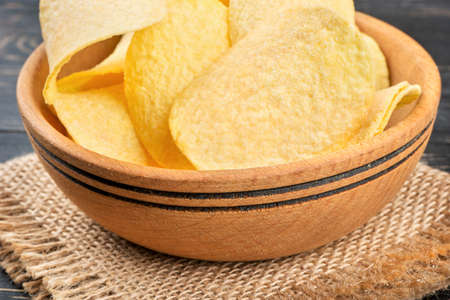 Bowl with potato chips on burlap on a dark table closeup
