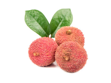 Three ripe lychee fruit in the shell and with leaves on white background