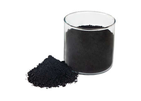 Black powder activated charcoal in glass on white background