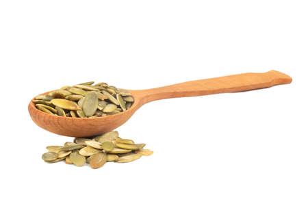 Pumpkin seed kernels in wooden spoon on white background