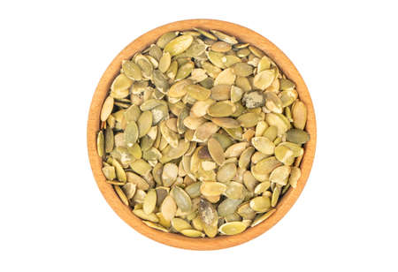 Pumpkin seeds without shell in a bowl on white background