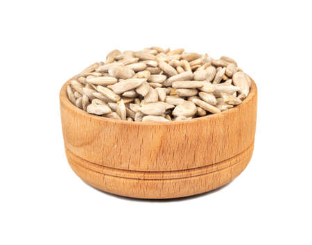 Sunflower seeds without shell in a wooden bowl on a white background