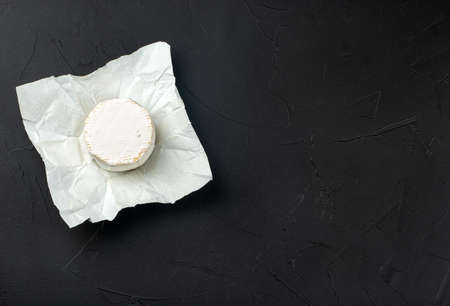 Round brie cheese in open paper package on dark concrete background, top view