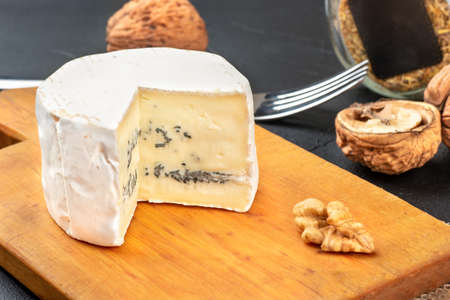 Slice of brie cheese with mold on a cutting board closeup with walnuts