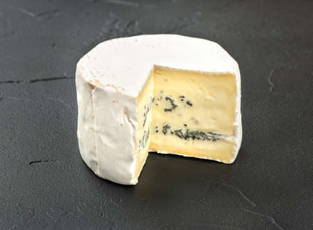Piece brie cheese with mold on dark background 写真素材
