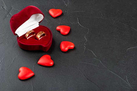 Two wedding rings with red box and hearts on concrete background Standard-Bild