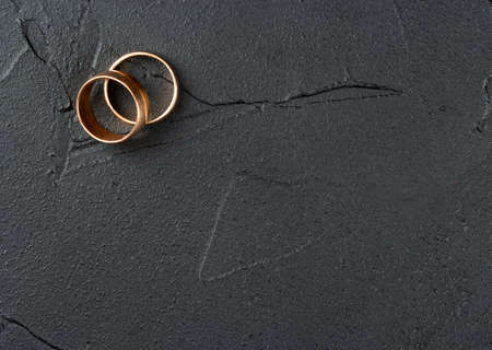 Two wedding rings on an empty dark concrete background, top view Reklamní fotografie