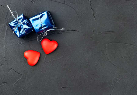 Two hearts with a gift on a dark background, top view