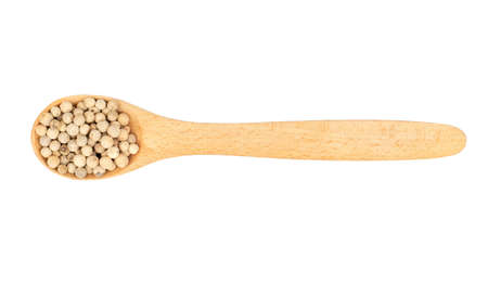 Small spoon with a white pepper on a light background, top view