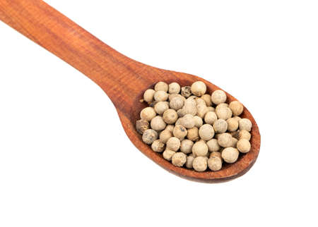 Small spoon with a white pepper on a light background