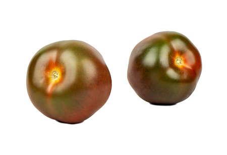 Two fresh kumato tomatoes on white background
