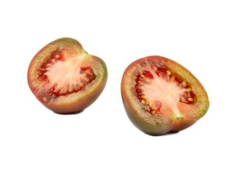 Two halves of juicy tomato kumato isolated on white background