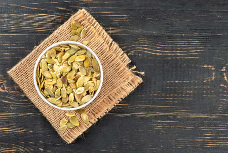 Pumpkin seeds without shell in a bowl on burlap and empty wooden background