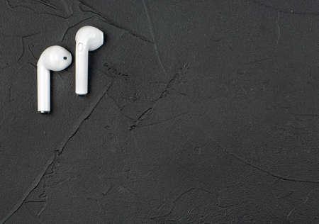White wireless headphones on dark concrete background, top view 스톡 콘텐츠