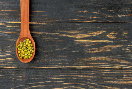 Spoon with green mung beans on wooden background, top view Imagens