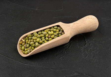 Wooden scoop with green mung beans on dark background Imagens