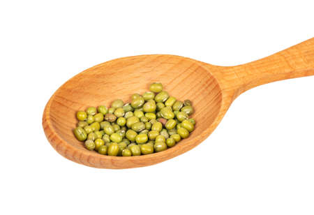 Several green mung beans in a large wooden spoon on a white background closeup