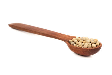 White pepper peas in wooden spoon on white background Imagens