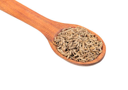 Spice dry cumin in wooden spoon closeup on white background Stock Photo