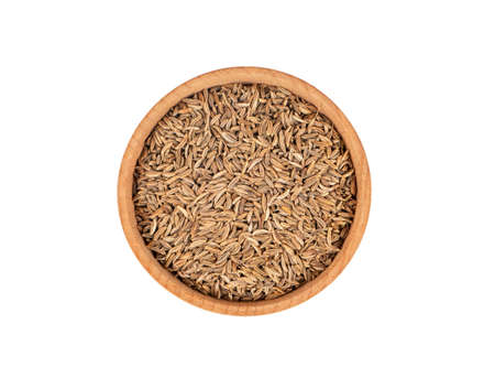 Dry cumin in wooden bowl isolated on white background, top view Stock Photo