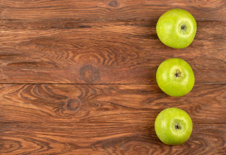 Three ripe green apples on a wooden background, top view Фото со стока