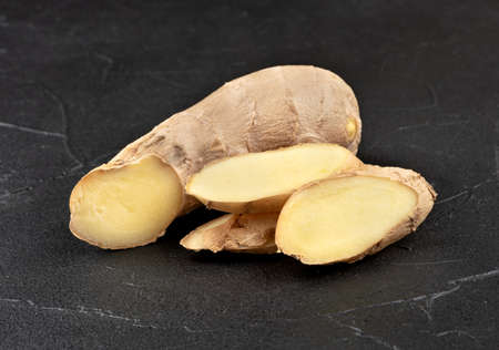Piece of ginger root with slices on dark background Фото со стока