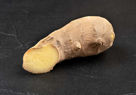 Fresh ginger root piece on dark concrete background Фото со стока - 125684713