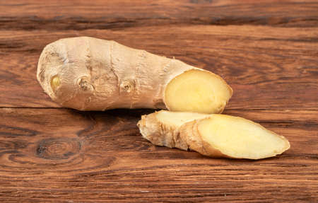 Piece of ginger root with slices on wooden background Фото со стока