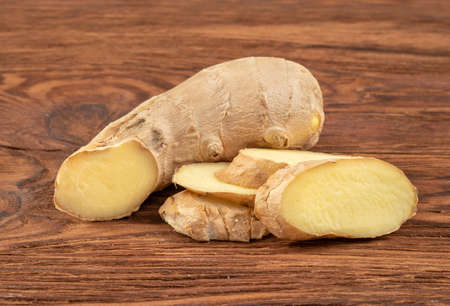 Piece of ginger root with slices on wooden background Фото со стока - 125684722