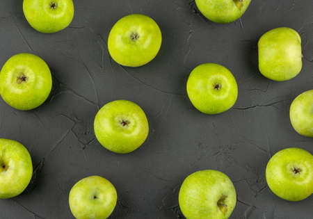 Scattered green apples on a dark concrete background, top view