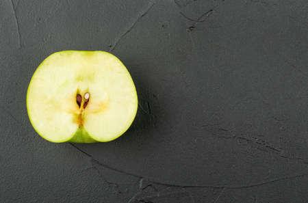 Half ripe apple on empty dark background, top view