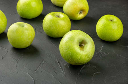 Scattered green apples on a dark concrete background