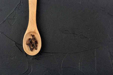 Dry cloves in a small wooden spoon on a dark background, top view