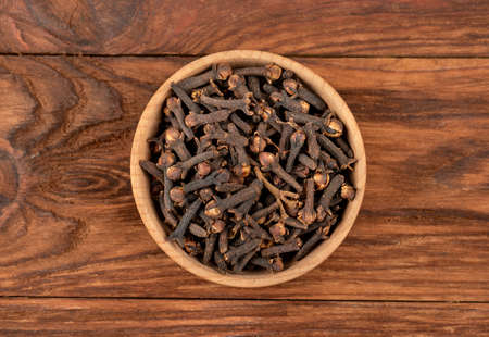 Bowl with seasoning dry cloves on a wooden background, top view Фото со стока - 127153378
