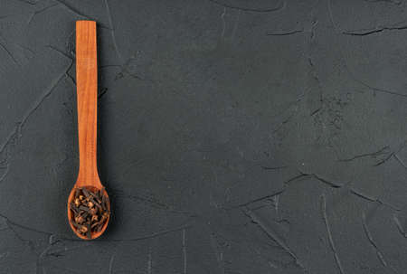 Dry cloves in wooden spoon on empty dark background, top view