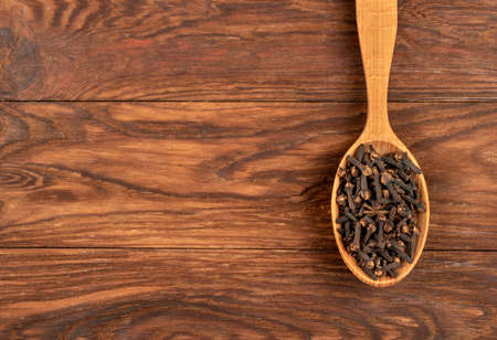 Spoon with dry cloves on wooden background, top view
