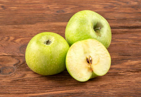 Two green apples with half on wooden background