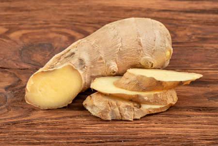 Piece of ginger root with slices on wooden background Фото со стока - 127153408