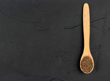 Small spoon with dry cumin on an empty dark background Фото со стока